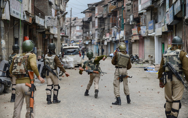 Indian police throw stones during clashes with flood-affected Kashmiri residents protesting against the state government in Srinagar on October 15, 2014. Kashmir was devastated last month by heavy monsoon rains and floods which killed more than 450 people in the region and caused billions of dollars in damage to homes, businesses and livelihoods.  Residents accuse the local government of a tardy response to the floods. (Photo by Tauseef Mustafa/AFP Photo)