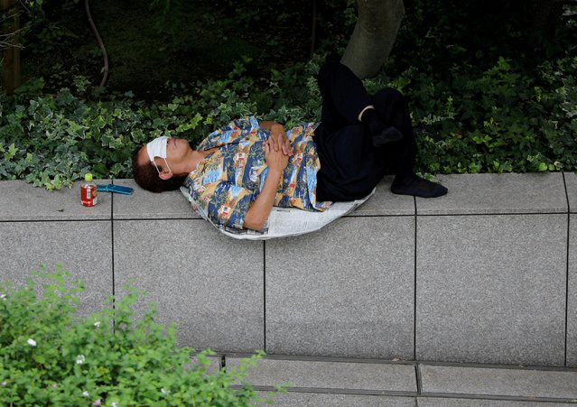 A man takes a nap on the street using a protective mask amid the coronavirus disease (COVID-19) outbreak, in Tokyo, Japan on July 16, 2020. (Photo by Issei Kato/Reuters)
