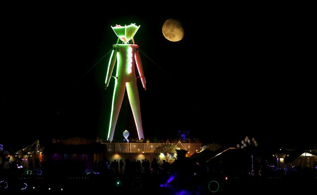 """The moon rises behind the Man during the Burning Man 2015 """"Carnival of Mirrors"""" arts and music festival in the Black Rock Desert of Nevada, September 1, 2015. (Photo by Jim Urquhart/Reuters)"""