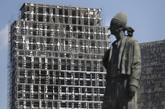 A statue representing the Lebanese expatriate is seen in front of a building that was damaged by an explosion that hit the seaport of Beirut, Lebanon, Wednesday, Aug. 5, 2020. Residents of Beirut confronted a scene of utter devastation on Wednesday, a day after a massive explosion at the port rippled across the Lebanese capital, killing at least 100 people, wounding thousands and leaving entire city blocks flooded with glass and rubble. (Photo by Hussein Malla/AP Photo)