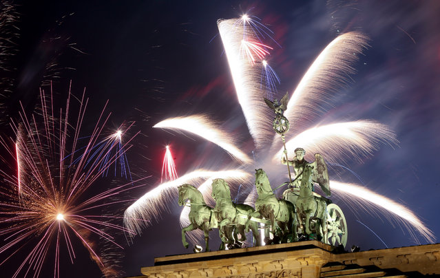 Fireworks explode over the Brandenburg Gate during New Year's festivities on January 1, 2018 in Berlin, Germany. Tens of thousands of revelers gathered in the city center to celebrate New Year's Eve. (Photo by Adam Berry/Getty Images)