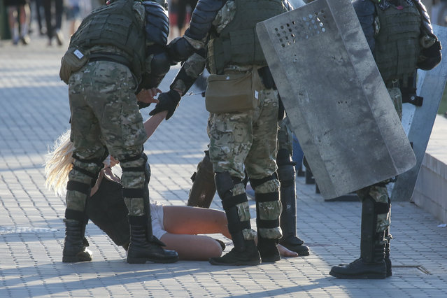 Belarussian policemen detain a woman in central Minsk on August 11, 2020. (Photo by Uladz Hrydzin/Radio Free Europe/Radio Liberty)