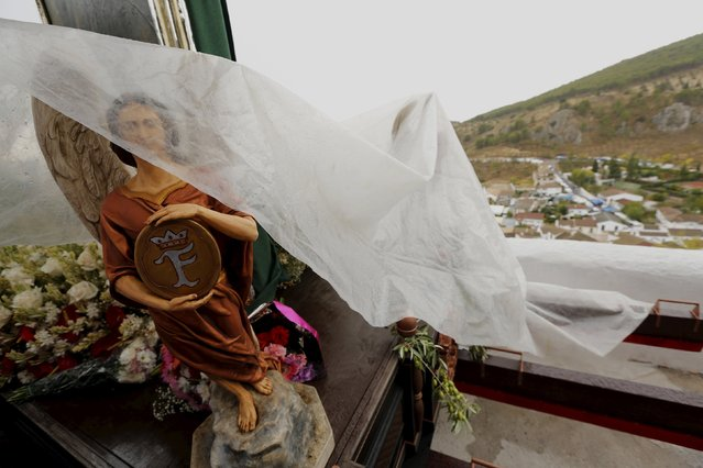 A statue of an angel is covered by a sheet of plastic from the rain during the Christ of Pano pilgrimage in Moclin, southern Spain, October 5, 2015. (Photo by Marcelo del Pozo/Reuters)