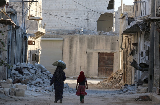 Civilians walk past damaged buildings in the rebel-held al-Sheikh Said neighbourhood of Aleppo, Syria September 1, 2016. (Photo by Abdalrhman Ismail/Reuters)