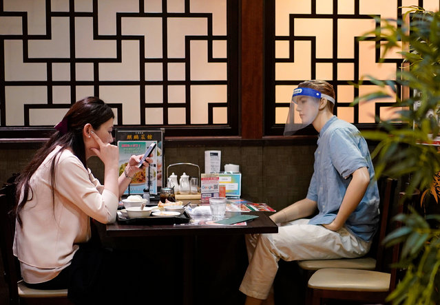 A young woman looks at her smartphone sitting in front of a mannequin use to keep social distancing at a Chinese cuisine restaurant in Tokyo, Japan, 27 July 2020. Japan's total number of COVID-19 cases crossed the 30,000 line showing the new coronavirus pandemic is spreading across the country and not only in Tokyo and Osaka megalopolis. (Photo by Franck Robichon/EPA/EFE)
