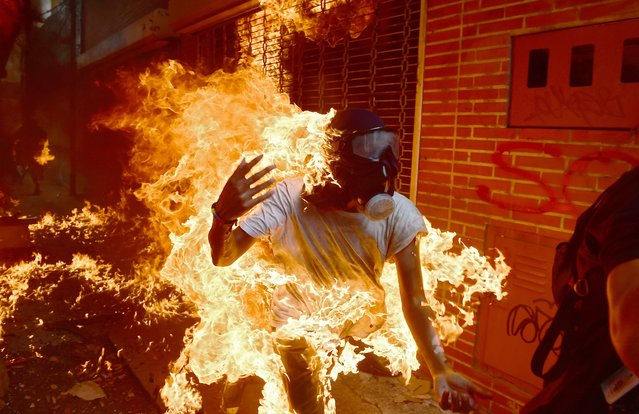 A demonstrator catches fire during clashes with riot police within a protest against Venezuelan President Nicolas Maduro, in Caracas on May 3, 2017. Venezuela's angry opposition rallied Wednesday vowing huge street protests against President Nicolas Maduro's plan to rewrite the constitution and accusing him of dodging elections to cling to power despite deadly unrest. (Photo by Ronaldo Schemidt/AFP Photo)