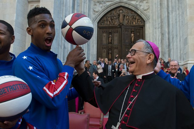 Bishop Dominick Lagonegro spins a basketball on his finger with the help of the Harlem Globetrotters in front of St. Patrick's Cathedral during the Columbus Day Parade on Fifth Ave. in the Manhattan borough of New York, October 12, 2015. (Photo by Stephanie Keith/Reuters)