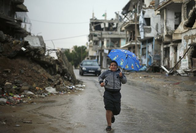 A Palestinian boy holds an umbrella as he runs near houses that witnesses said were destroyed or damaged by Israeli shelling during the most recent conflict between Israel and Hamas, on a rainy day in the east of Gaza City November 16, 2014. (Photo by Suhaib Salem/Reuters)