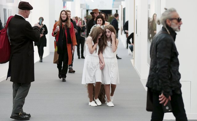 "Twin sisters who are part of a performance artwork entitled ""Siamese Hair Twins"" by Tunga, walk through the galleries at the Frieze Art Fair in London, Britain October 14, 2015. (Photo by Suzanne Plunkett/Reuters)"