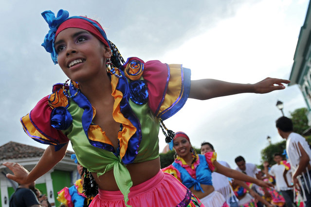 "A girl takes part in the ""Burial of arrogance and haughtiness"" carnival during the IX Poetry Festival in Granada, 45 km from Managua, Nicaragua on February 20, 2013. In this occasion the festival is dedicated to Nicaraguan poet Ernesto Cardenal. (Photo by Hector Retamal/AFP Photo)"