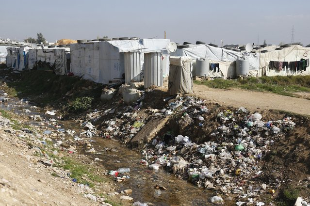 A garbage filled-area is seen near the tents of Syrian refugees at a camp in Zahle in the Bekaa valley November 18, 2014. (Photo by Mohamed Azakir/Reuters)