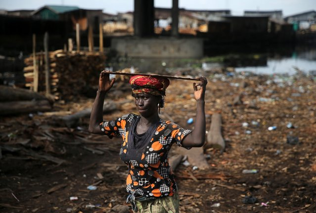 A woman carries a plank on her head at Okobaba sawmill at the edge of the Lagos Lagoon June 24, 2014. (Photo by Akintunde Akinleye/Reuters)