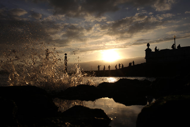 Small waves break at the Tagus riverbank as people take photographs at the Cais das Colunas dock in downtown Lisbon, Sunday, November 16, 2014. The place is a popular location for locals and tourists to pause, relax or take photographs. (Photo by Francisco Seco/AP Photo)