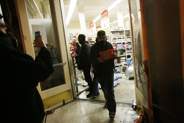A man leaves a Smart & Final food and supply store during a demonstration following the grand jury decision in the Ferguson, Missouri shooting of Michael Brown, in Oakland, California November 25, 2014. (Photo by Stephen Lam/Reuters)