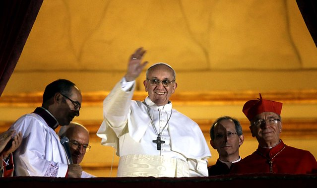 Pope Francis waves to the crowd from the central balcony of St. Peter's Basilica at the Vatican, March 13, 2013. Cardinal Jorge Bergoglio of Argentina, who chose the name of Francis, is the 266th pontiff of the Roman Catholic Church. (Photo by Gregorio Borgia/Associated Press)