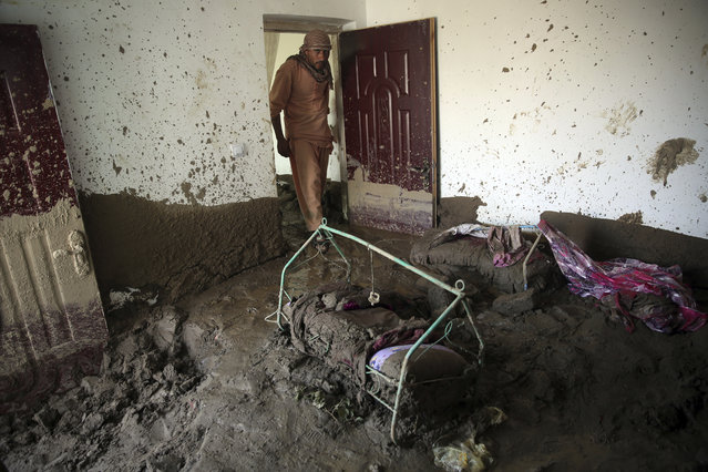 An Afghan man looks for belongings in his house that was damaged by a mudslide, in Parwan province, north of Kabul, Afghanistan, Thursday, August 27, 2020. The death toll from heavy flooding in northern and eastern Afghanistan rose to at least 150 on Thursday, with scores more injured as rescue crews searched for survivors beneath the mud and rubble of collapsed houses, officials said. (Photo by Rahmat Gul/AP Photo)