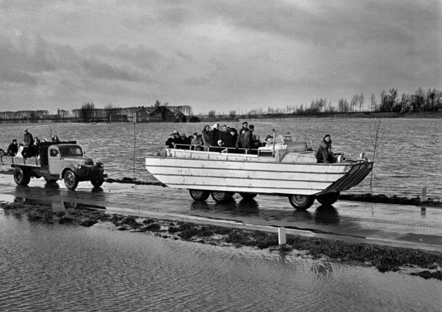 A loaded amphibian tows a broken down lorry, also loaded with refugees, during rescue operations on the devastated Zuid Beveland, Holland, February 6, 1953.  Gale force Spring tides, which swamped European coastlines, on the night of January 31, caused extensive damage in low-lying Holland, where the known death toll already exceeds 1,200. (Photo by AP Photo)