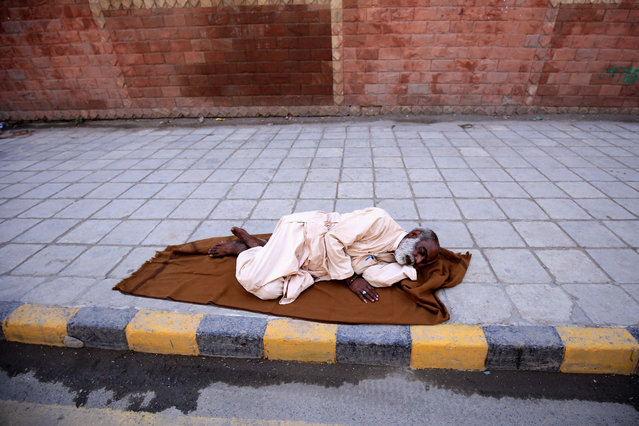 An elderly Pakistani man sleeps on a road side in Peshawar, Pakistan, 01 October 2020. The UN observes 01 October as an International Day for Old Persons with this year's theme being Sustainability and Age Inclusiveness in the Urban Environment. (Photo by Arshad Arbab/EPA/EFE)