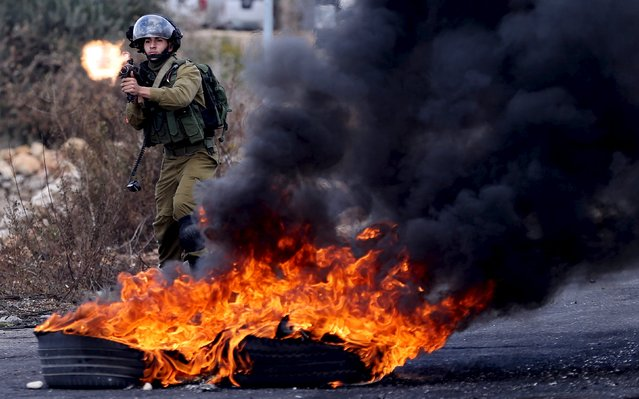 An Israeli soldier fires a weapon towards Palestinian protesters during clashes near the Jewish settlement of Bet El, near the West Bank city of Ramallah October 30, 2015. Knife-wielding Palestinians attacked Israelis in Jerusalem and the Israeli-occupied West Bank on Friday and one assailant was shot dead, police said, extending a wave of violence spurred in part by tensions over a Jerusalem holy site. (Photo by Mohamad Torokman/Reuters)