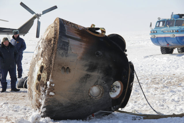 The Soyuz TMA-06M spacecraft lies passively on its side March 16 after bringing home Expedition 34 Commander Kevin Ford of NASA, Soyuz Commander Oleg Novitskiy and Flight Engineer Evgeny Tarelkin to a landing northeast of Arkalyk, Kazakhstan following a one-day delay due to inclement weather in the area. The Soyuz initially landed upright before being tilted on its side for servicing after touching down to wrap up 144 days in space and 142 days for Ford, Novitskiy and Tarelkin at the International Space Station. The three crewmembers were flown by helicopter to Kustanai, Kazakhstan en route to their homes in Houston and Star City, Russia. (Photo by Sergey Vigovskiy/NASA/The Atlantic)