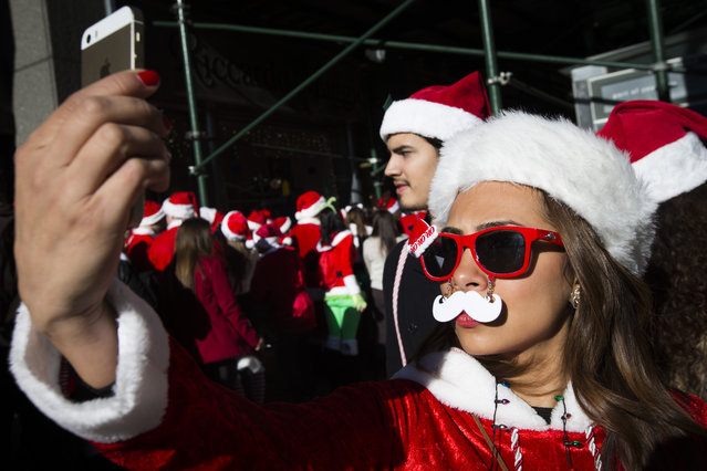 A reveler dressed in a holiday theme costume takes a selfie during SantaCon, Saturday, December 13, 2014, in New York. (Photo by John Minchillo/AP Photo)