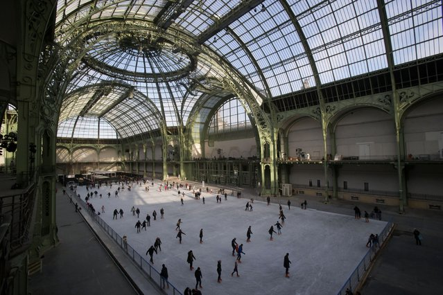 People ice skate at the Grand Palais in Paris, Sunday, December 14, 2014. The Grand Palais skating rink opened to the public on Sunday and is the largest temporary ice rink created in France during the winter holiday. (Photo by Michel Euler/AP Photo)