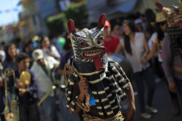"A participant wearing a tiger mask performs during the ""Paseo del Pendon"", a traditional artistic march in Chilpancingo,  December 21, 2014. The ""Paseo del Pendon""  (walk banner)  is a traditional celebration in the streets of Chilpancingo to mark the begin of the the year-end festivities in the city. (Photo by Jorge Dan Lopez/Reuters)"