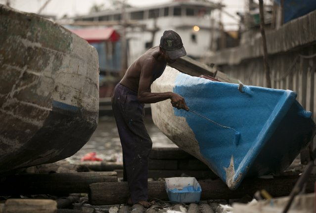 A man paints a boat he has repaired on a floating dock in Luar Batang in north Jakarta in this October 7, 2014 file photo. (Photo by Darren Whiteside/Reuters)