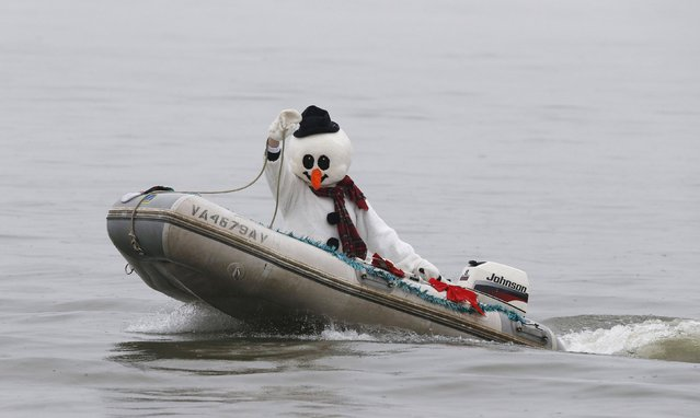 A boater, dressed as Frosty the Snowman, takes part in the 29th annual Christmas Eve water performance on the Potomac River in Alexandria, Virginia, December 24, 2014. (Photo by Larry Downing/Reuters)