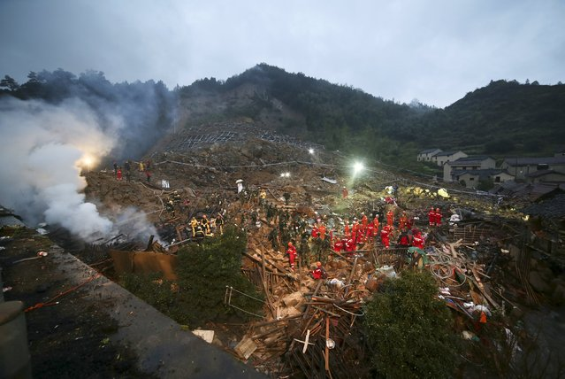 Rescuers search for survivors among debris at the site of a landslide in Yaxi township of Lishui, Zhejiang province, China, November 14, 2015. A landslide occurred on Friday night in Lishui and buried over 20 houses underneath. Four people are confirmed dead and 33 others remained missing, local media reported. (Photo by Reuters/Stringer)