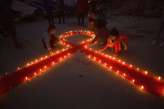 Nepalese people lit candles around the symbol of RED AIDS during Eve of the 33rd World AIDS Day celebrated in Kathmandu, Nepal on Monday, November 30, 2020. World AIDS Day is celebrated worldwide on December 1st of every year to raise the awareness in the fight against HIV. (Photo by Narayan Maharjan/NurPhoto via Getty Images)