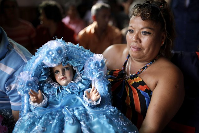 A Catholic faithful holds a figurine of baby Jesus during a religious procession on Holy Innocents Day in Antiguo Cuscatlan, on the outskirts of San Salvador, December 28, 2014. Festivities are held every December 28 in honor of children, termed the Holy Innocents, below the age of two who were ordered to be killed by King Herod, according to biblical passages. (Photo by Jose Cabezas/Reuters)