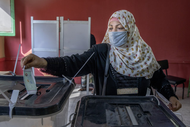 A woman casts her ballot on the first day of the parliamentary election inside a polling station in Giza, Egypt, Saturday, October 24, 2020. Egyptians began voting Saturday in the first stage of a parliamentary election, a vote that is highly likely to produce a toothless House of Representatives packed with supporters of President Abdel-Fattah el-Sissi. (Photo by Nariman El-Mofty/AP Photo)