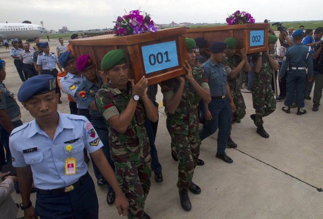 Indonesian military carry the caskets containing the bodies of two AirAsia flight QZ8501 passengers recovered off the coast of Borneo at a military base in Surabaya December 31, 2014. (Photo by Sigit Pamungkas/Reuters)