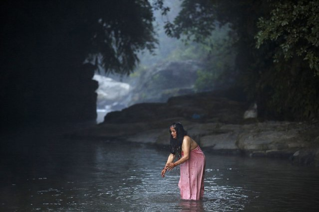 A devotee takes a holy bath in the River Saali in Sankhu on the first day of Swasthani Brata Katha festival in Kathmandu January 5, 2015. (Photo by Navesh Chitrakar/Reuters)