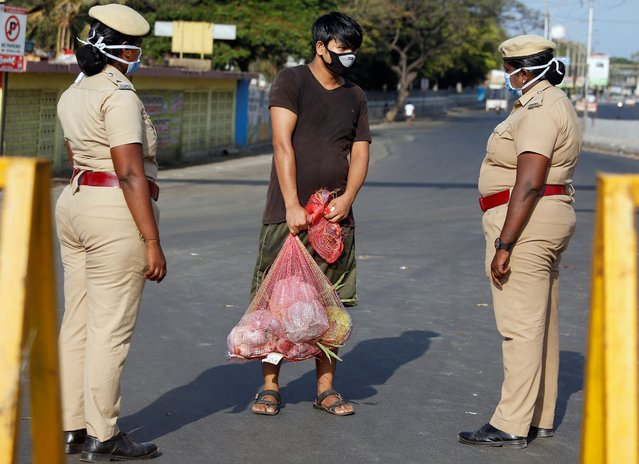A man carrying vegetables is stopped by police at a barricade on a road during a 21-day nationwide lockdown to limit the spreading of coronavirus disease (COVID-19) in Chennai, India, March 25, 2020. (Photo by P. Ravikumar/Reuters)