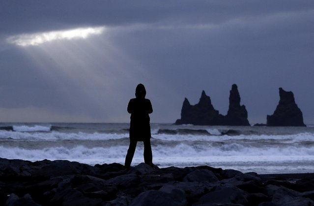 A woman stands on the black beach in Vik, Iceland, near the Volcano Katla, Friday, October 28, 2016. (Photo by Frank Augstein/AP Photo)