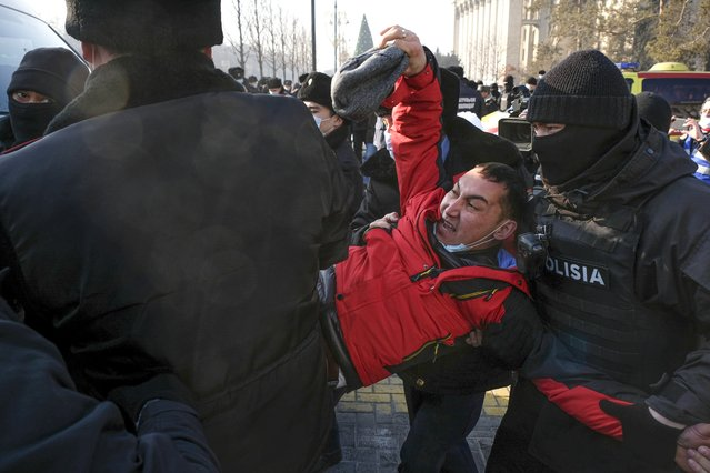 Kazakhstan's police officers detain a protester during an opposition rally in Almaty, Kazakhstan, Sunday, January 10, 2021, as voters in resource-rich Kazakhstan are going to the polls in a parliamentary election lacking any serious opposition. (Photo by Vladimir Tretyakov/AP Photo)