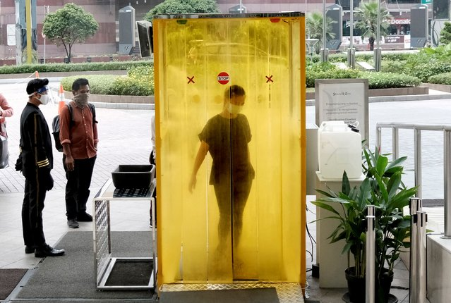 A woman reacts as she is sprayed with disinfectant inside a chamber as a precaution against the new coronavirus before entering a shopping mall in Jakarta, Indonesia, Tuesday, June 9, 2020. As Indonesia's overall virus caseload continues to rise, the capital city has moved to restore normalcy by lifting some restrictions this week, saying that the spread of the virus in the city of 11 million has slowed after peaking in mid-April. (Photo by Dita Alangkara/AP Photo)
