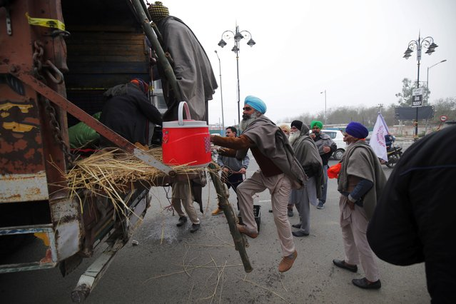 """Farmers board a tractor trolley as they begin their march towards New Delhi to join farmers taking part in sit-in protest against the new agriculture laws and demanding to repeal the laws at New Delhi borders, in Amritsar, India, 12 January 2021. Farmers' organizations have proposed to take out a """"parallel parade"""" on the day of India's Republic Day and its parade to be held at New Delhi, on 26 January 2021. Scores of tractor trolleys are expected to move towards Delhi between 12-15 January from Punjab and Haryana in preparations for the """"parallel parade"""". However, the Supreme Court on 12 January has put a hold on the new controversial agriculture laws and has formed a four-member panel to hold talks with the farmers on the issue. (Photo by Raminder Pal Singh/EPA/EFE)"""