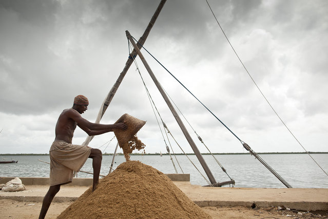 """""""Symmetry"""". A worker in Lamu piles sand on a boat dock. Location: Lamu, Kenya.  (Photo and caption by Robin Moore/National Geographic Traveler Photo Contest)"""