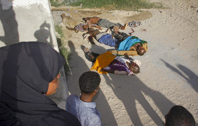 Somalis look at the bodies of five people killed during a raid in the Lower Shabelle region and then brought to the Madina hospital in Mogadishu, Somalia Thursday, May 10, 2018. Somali intelligence officials say U.S. and Somali commandos seized three men thought to be commanders with the al-Shabab extremist group during the deadly raid, while a local elder said five people thought to be banana farmers were killed in the raid late Wednesday. (Photo by Farah Abdi Warsameh/AP Photo)