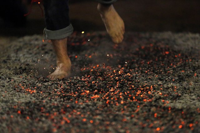 A reveler rushes through burning embers during the night of San Juan in San Pedro Manrique, Soria province in northern Spain, on June 24, 2013. (Photo by Cesar Manso/AFP Photo)