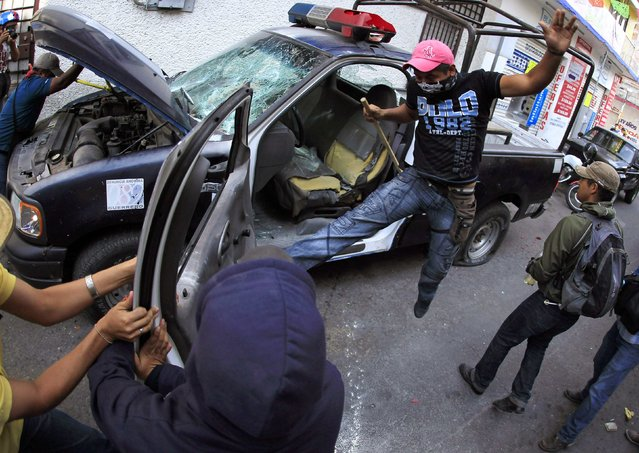 Demonstrators destroy a police patrol vehicle during a protes by relatives of the 43 missing students from the Ayotzinapa Teacher Training College outside the federal court in Chilpancingo, in the Mexican state of Guerrero, January 19, 2015. The protest was held to urge the federal court to bring charges of enforced disappearance and murder against the former mayor of Iguala, Jose Luis Abarca. (Photo by Jorge Dan Lopez/Reuters)