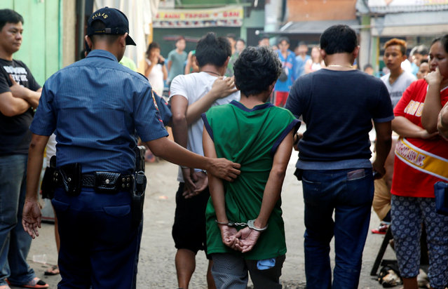 Policemen escort two men who were detained because of pending criminal court cases, during an anti-drugs operation in Mandaluyong, Metro Manila in the Philippines, November 10, 2016. (Photo by Erik De Castro/Reuters)