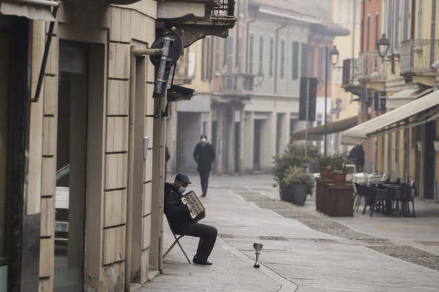 A man plays an accordion in Codogno, northern Italy, Sunday, February 21, 2021. The first case of locally spread COVID-19 in Europe was found in the small town of Codogno, Italy one year ago on February 21st, 2020. The next day the area became a red zone, locked down and cutoff from the rest of Italy with soldiers standing at roadblocks keeping anyone from entering of leaving. (Photo by Luca Bruno/AP Photo)