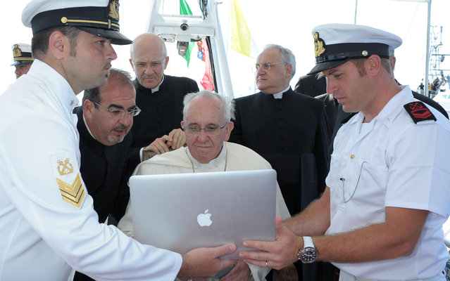 This handout picture released by the Vatican press office on July 8, 2013 shows Pope Francis  looking at a computer while receiving explanations on a boat off Lampedusa island, a key destination of tens of thousands of would-be immigrants from Africa, during his visit on July 8, 2013. In a visit stripped of the usual pomp of papal travel, Francis will cast a wreath into the sea and hold a mass of mourning with a simple cross made from the wood of rickety fishing boats that migrants arrive on. (Photo by Osservatore Romano/AFP Photo)