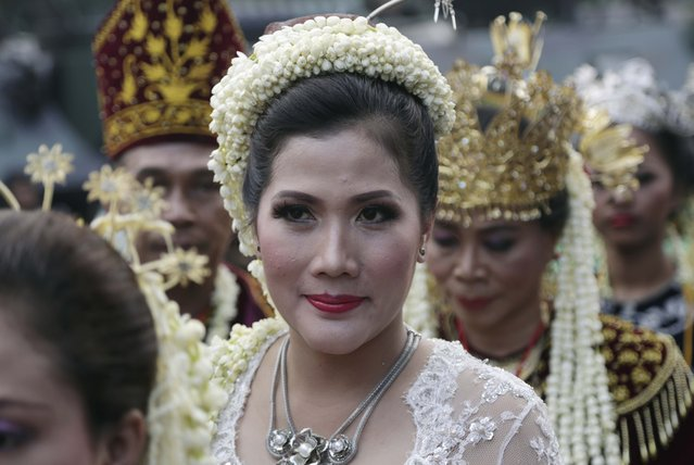 Brides and grooms walk during a mass wedding ceremony in Jakarta, Indonesia, Wednesday, January 28, 2015. (Photo by Achmad Ibrahim/AP Photo)