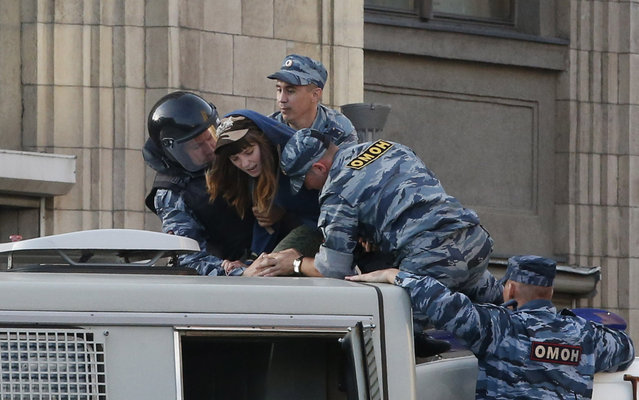 Policemen detain a woman on a police truck during a protest against the verdict of a court in Kirov, which sentenced Russian opposition leader Alexei Navalny to five years in jail, in central Moscow, July 18, 2013. Russian opposition leader Alexei Navalny was sentenced to five years in jail for theft on Thursday, an unexpectedly tough punishment which supporters said proved President Vladimir Putin was a dictator ruling by repression. (Photo by Grigory Dukor/Reuters)