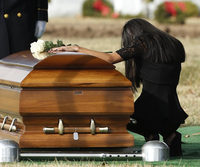 Christina Strange grieves over the casket of U.S. Sergeant First Class Ramon Morris of New York City, at Arlington National Cemetery January 23, 2015. Strange is the mother of Ramon's daughter, Ariana Morris. Ramon was killed in action in December of 2014 in Parwan Province, Afghanistan from injuries caused by an IED. (Photo by Gary Cameron/Reuters)